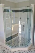custom glass shower enclosure in room with hexagonal tiles